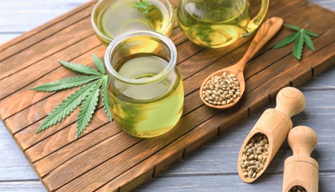 hemp-sourced-cbd-oil-in-glass-jar-on-wooden-cutting-board-with-hemp-seeds-and-leaf