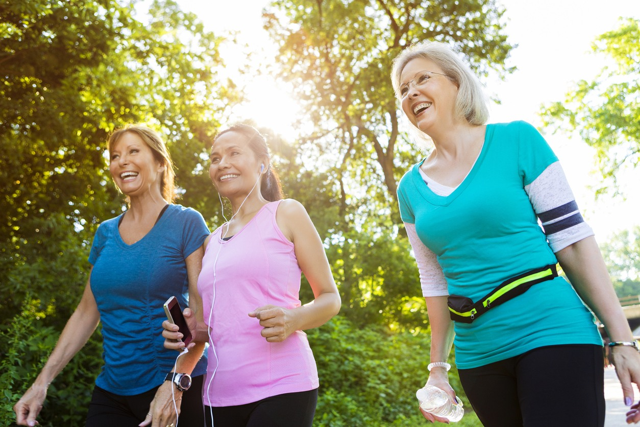 group of female senior friends out for a walk on sunny trail near trees