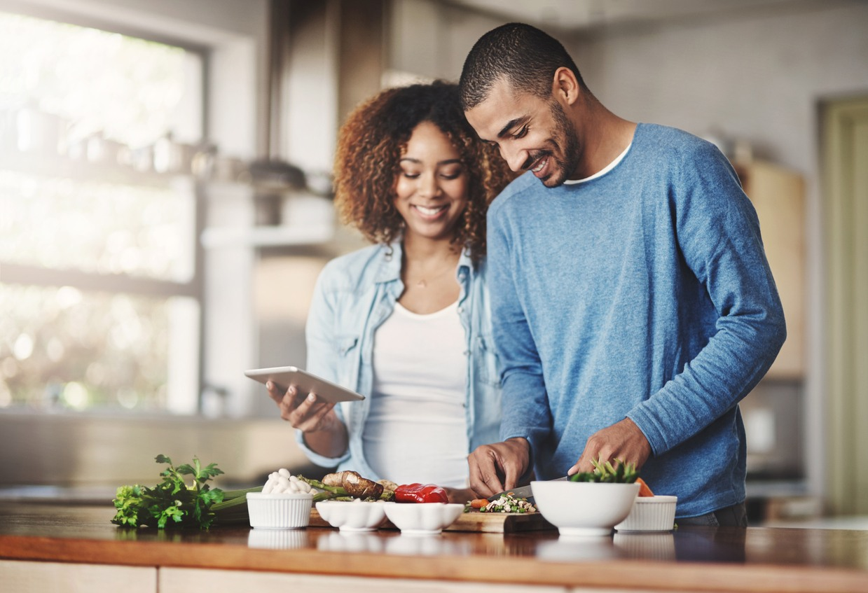 happy-young-couple-in-kitchen-preparing-healthy-meal-from-ingredients-in-white-bowls