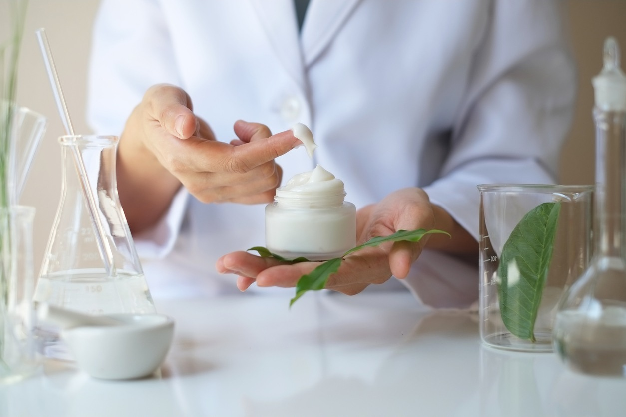 scientist-holding-completed-moisturizer-near-ingredients-in-flasks-and-bowls