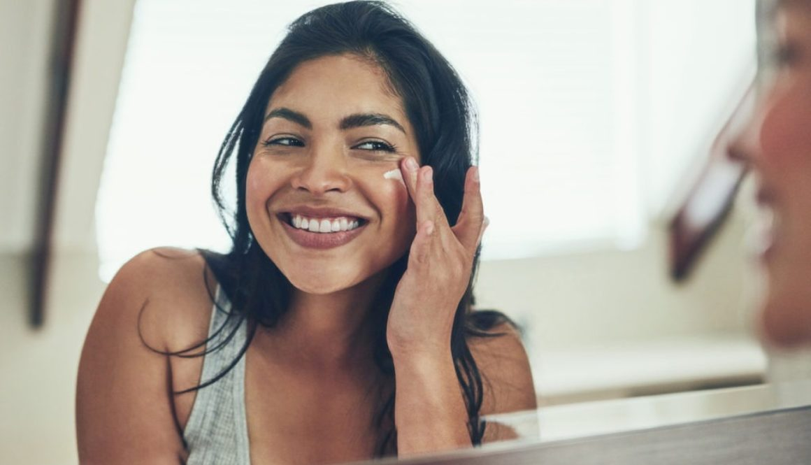 young-woman-smiling-while-applying-moisturizer-to-cheek