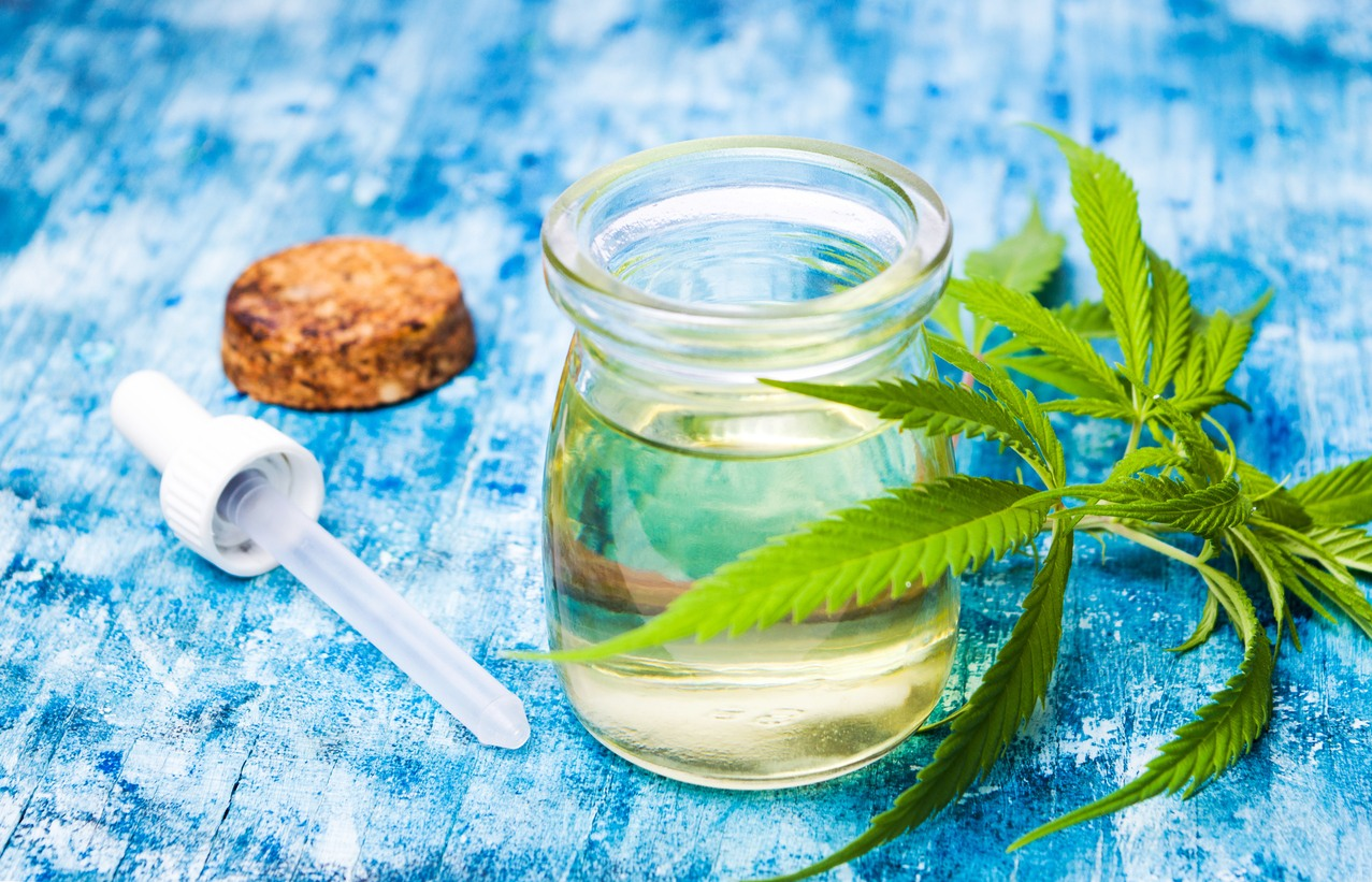glass-container-of-hemp-cbd-oil-on-table-with-dropper-and-cannabis-leaves