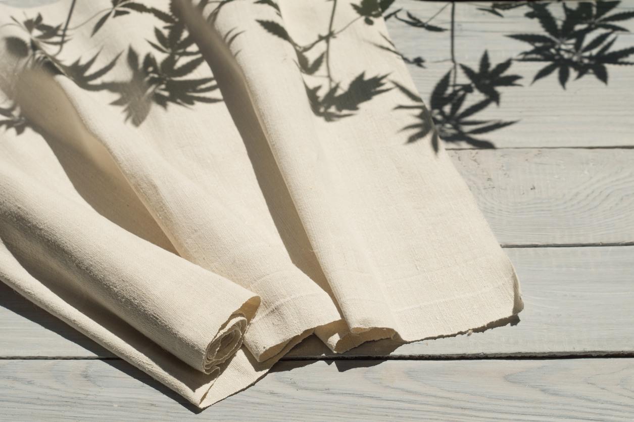 hemp-fabric-on-wooden-table-with-shadows-of-hemp-plants