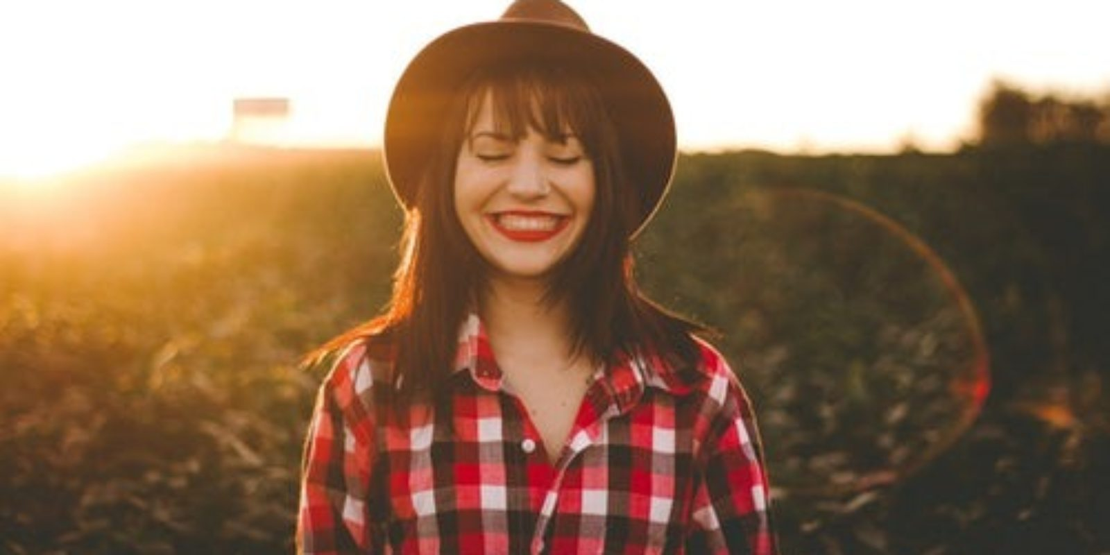 young-woman-wearing-brimmed-sunhat-and-red-checkered-shirt-smiling-in-field-during-golden-hour