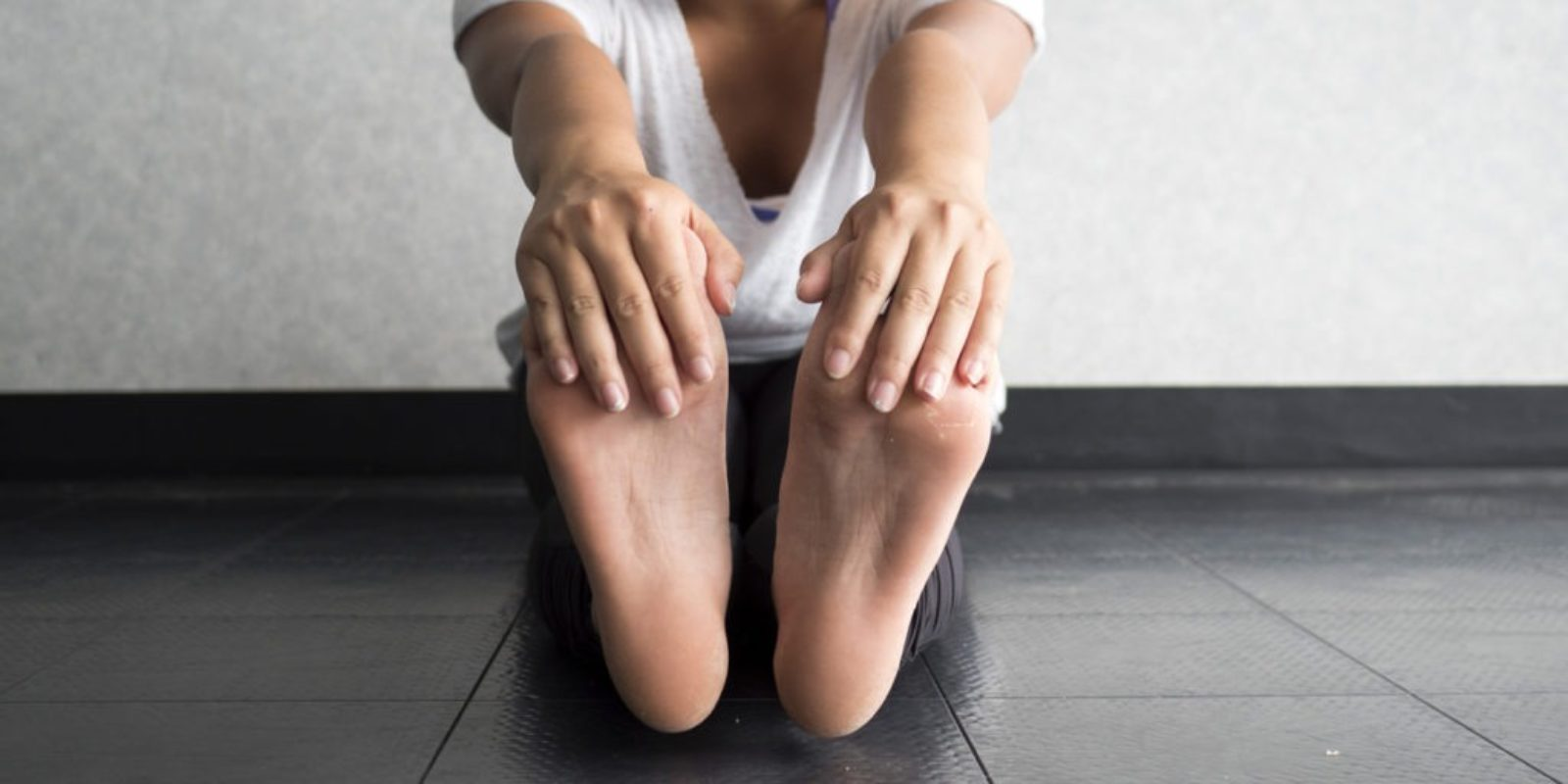 young woman sitting of floor with legs extended while holding toes to stretch hamstrings
