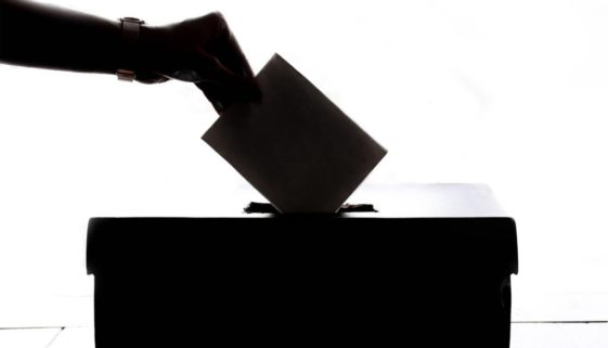 Person putting a vote into a box.
