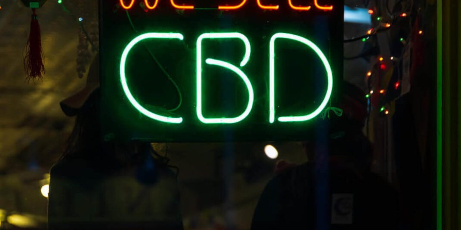 """We sell CBD"" neon sign in the window of a CBD Franchise"