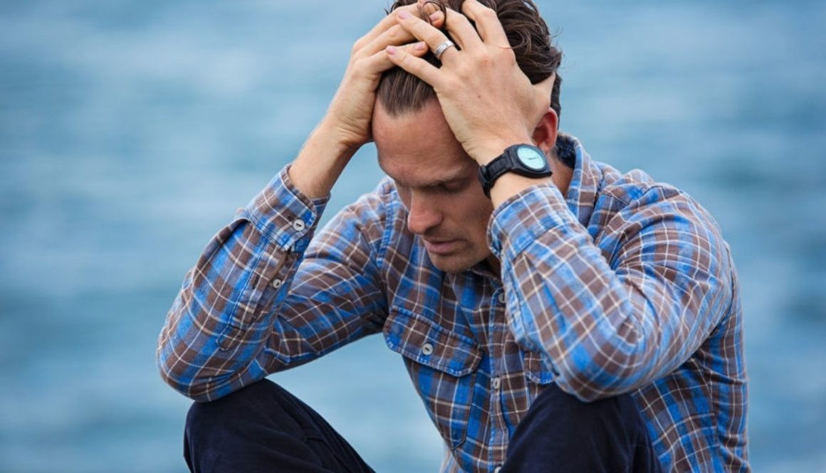 Man appears stressed out by holding his head and body crouched together.