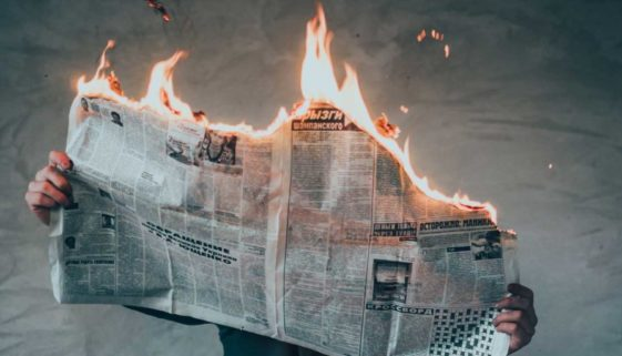Newspaper burning while a person is reading it.