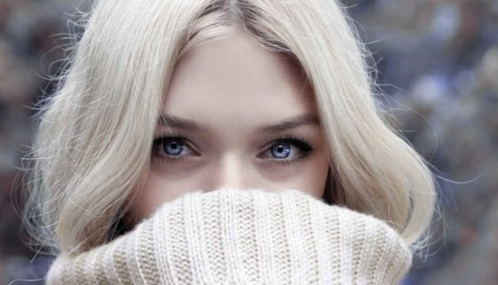 Beautiful woman covering her mouth with a turtleneck sweater.