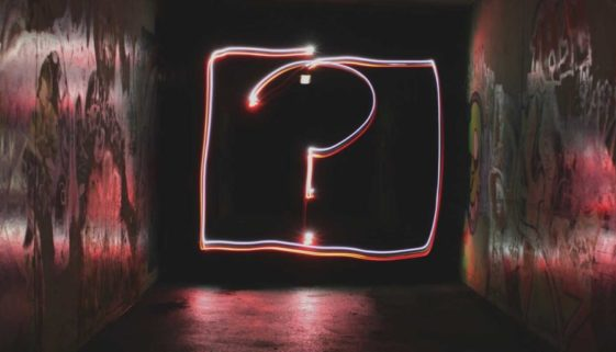 A question mark made with light in a tunnel.